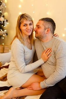 Casal feliz e apaixonado curtindo momentos ao lado de uma árvore de natal