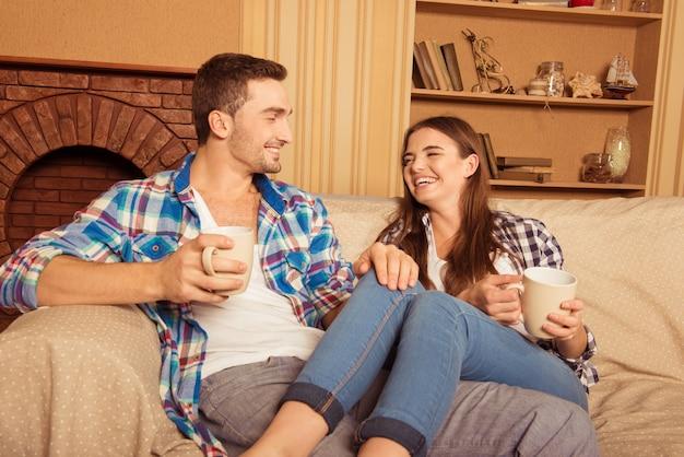 Casal feliz e apaixonado por copos sentado no sofá