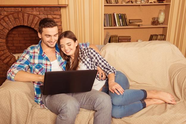 Casal feliz e apaixonado por laptop sentado no sofá