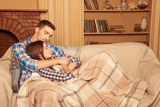 Casal feliz e apaixonado por xadrez sentado no sofá