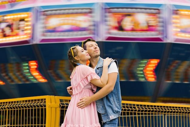 Casal feliz e apaixonado se divertindo em um parque de diversões