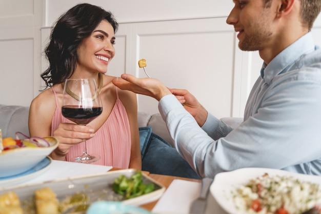 Casal feliz e apaixonado, sentado à mesa com comida deliciosa e vinho no restaurante