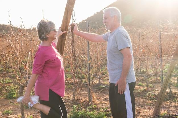 Casal feliz e ativo de idosos fazendo exercícios de alongamento ao ar livre juntos, sorrindo