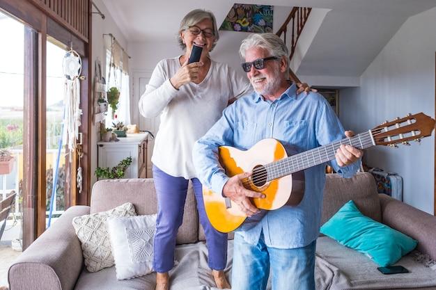 Casal feliz e engraçado de pessoas idosas e maduras se divertindo e curtindo em casa fazendo uma festa juntos, cantando e dançando tocando violão no interior. férias ou mesmo celebrando o conceito.