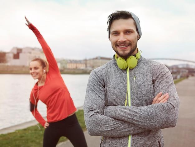 Casal feliz e esportivo posando contra o rio