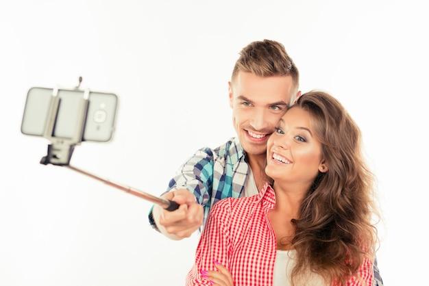 Casal feliz e fofo apaixonado fazendo foto de selfie com stick de selfie
