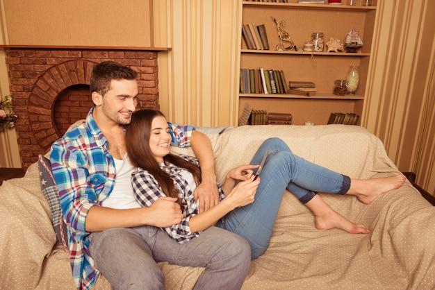 Casal feliz e fofo apaixonado servindo na rede no sofá