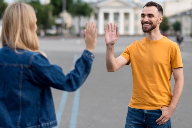 Casal feliz e gesto de mais cinco