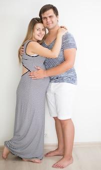 Casal feliz e grávida com roupas listradas, posando contra uma parede branca