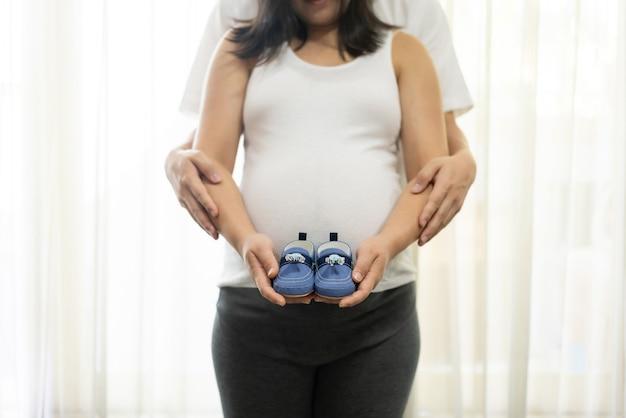 Casal feliz e grávida de marido e mulher. esperando jovem segura bebê na barriga de grávida.