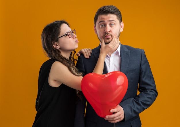 Casal feliz e lindo, homem e mulher com balão vermelho em forma de coração, feliz no amor, comemorando o dia dos namorados na parede laranja