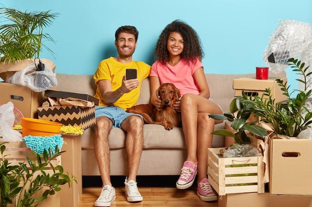 Casal feliz e relaxado no sofá com um cachorro cercado de caixas de papelão
