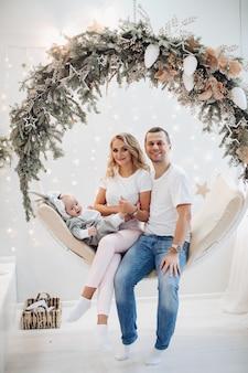 Casal feliz e seu adorável bebê posando para a foto do conceito de natal