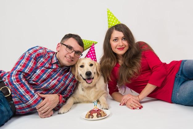 Casal feliz e seu cachorro comemoram o aniversário de um ano