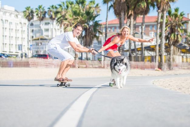 Casal feliz e seu cão husky fazendo esporte