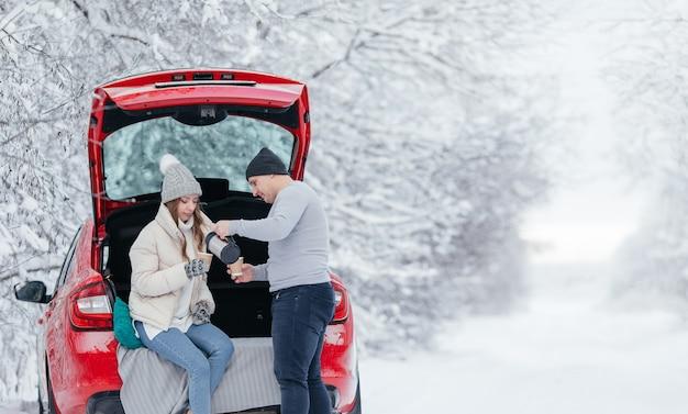 Casal feliz e sorridente de viajantes bebe café ou chá com uma garrafa térmica perto do carro vermelho na floresta de inverno