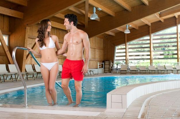 Casal feliz e sorridente desfrutando juntos de uma piscina térmica em um centro de spa