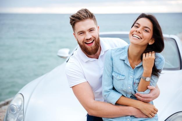 Casal feliz e sorridente em um encontro em pé perto de um carro à beira-mar