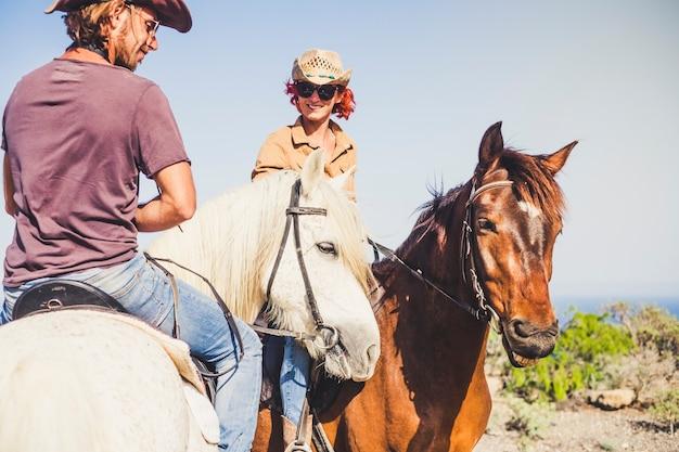 Casal feliz e sorridente fazendo um passeio a cavalo na natureza - atividade de lazer ao ar livre para jovens juntos em amizade com animais para terapia