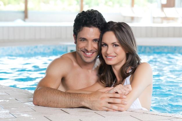 Casal feliz e sorridente, olhando para a câmera enquanto relaxa na beira de uma piscina