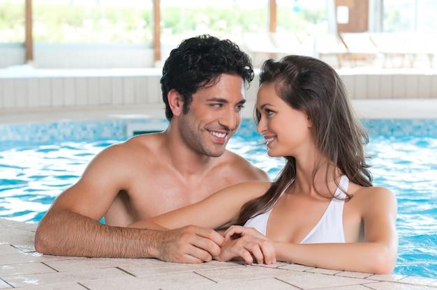 Casal feliz e sorridente relaxando juntos em uma piscina no clube de spa