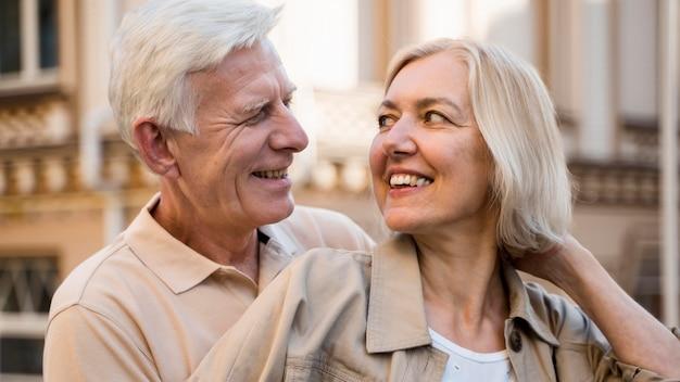 Casal feliz e sorridente se abraçando enquanto se diverte ao ar livre