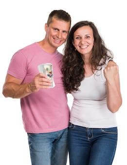 Casal feliz e sorridente segurando o dinheiro de um dólar em uma parede branca