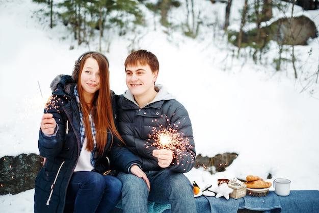 Casal feliz e sorridente sentado em um tronco com estrelinhas comemorando o natal ao ar livre na floresta de inverno