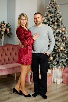 Casal feliz elegante sorrindo, abraçando as luzes de natal