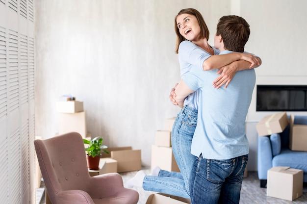 Casal feliz em casa se abraçando no dia da mudança