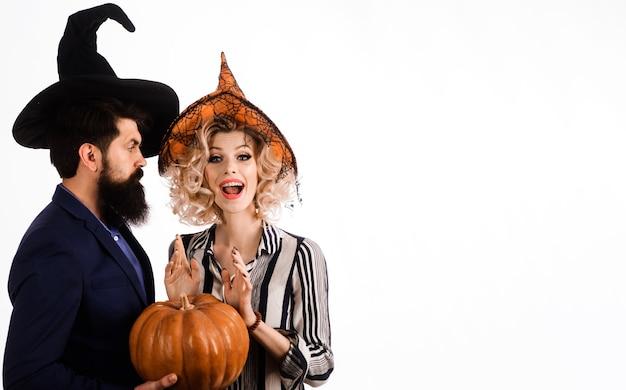 Casal feliz em chapéus de bruxas com abóbora. jovens vestidos de halloween. celebração e festa. 31 de outubro.