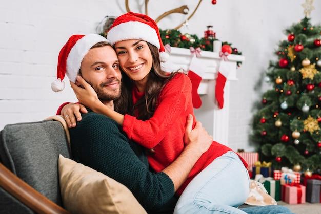 Casal feliz em chapéus de natal abraçando no sofá