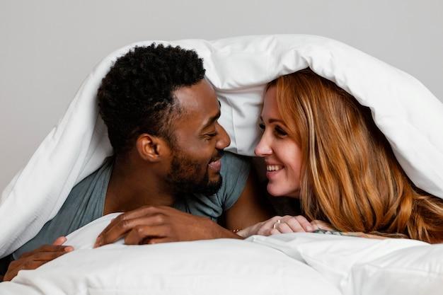 Casal feliz em close-up debaixo do cobertor