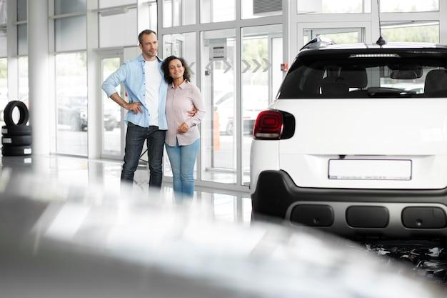 Casal feliz em concessionária de showroom de carros