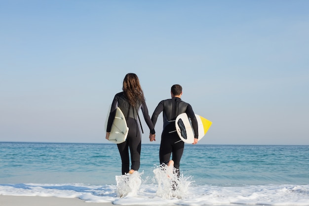 Casal feliz em fatos de mergulho com prancha de surf em um dia ensolarado