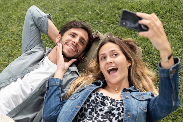 Casal feliz em foto média tirando fotos