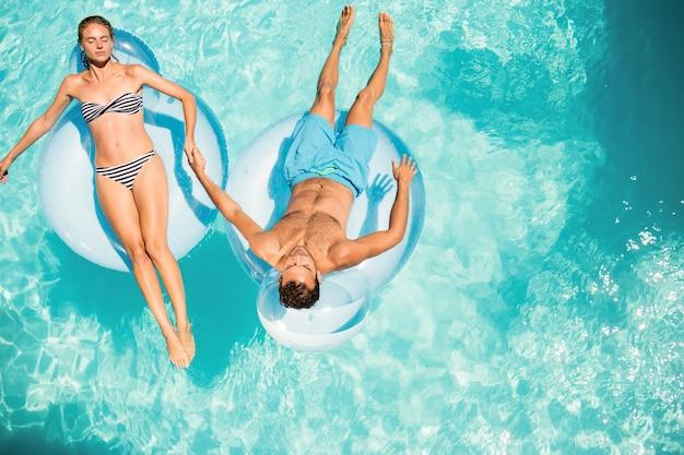 Casal feliz em lilos na piscina