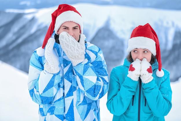Casal feliz em luvas quentes e chapéus de papai noel no resort nevado. férias de inverno