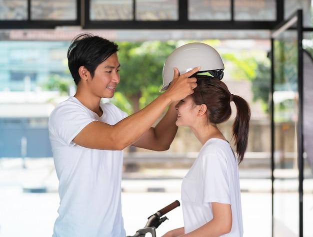 Casal feliz em pé e vestindo uma bicicleta capacete em casa antes de viajar