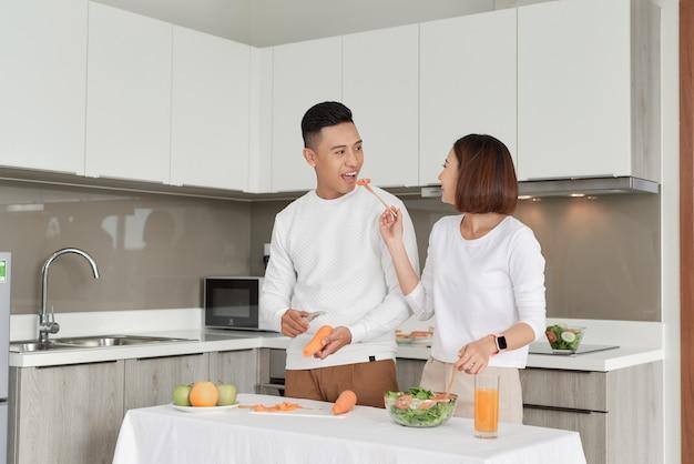 Casal feliz em pé na cozinha de casa preparando um jantar gostoso no primeiro namoro