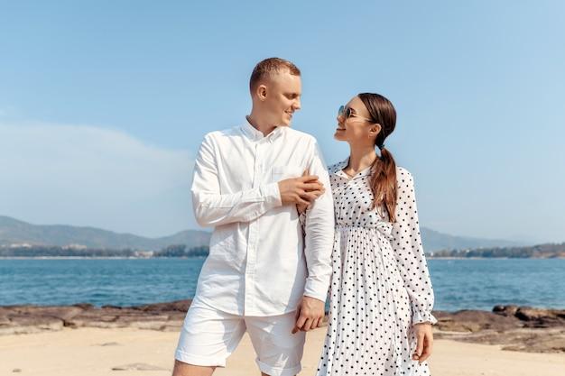 Casal feliz em pé na rocha olhando um para o outro
