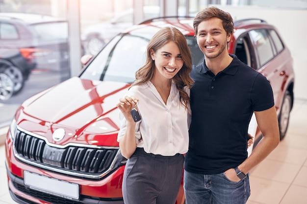 Casal feliz em pé perto de um carro novo na concessionária