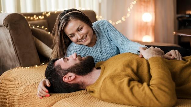 Casal feliz em plano médio deitado na cama