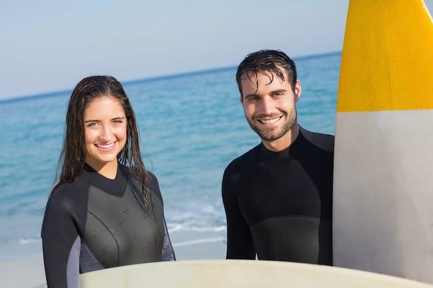 Casal feliz em roupa de mergulho com prancha em um dia ensolarado