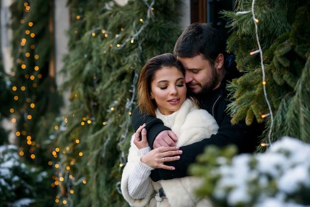 Casal feliz em roupas quentes, abraçando-se sobre a árvore de natal com luzes. férias de inverno, natal e ano novo.