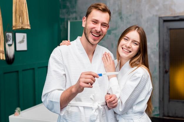 Casal feliz em roupões segurando o teste de gravidez
