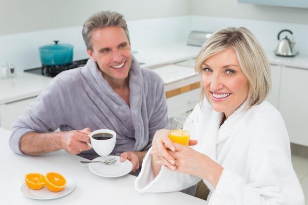 Casal feliz em roupões tomando café da manhã na cozinha