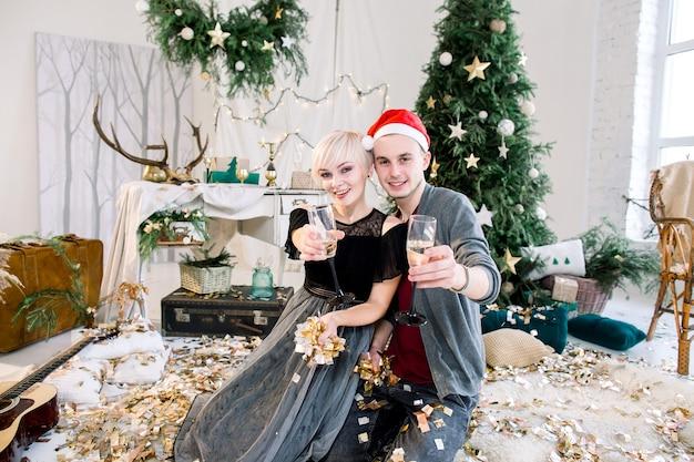 Casal feliz em sala decorada comemorando ano novo bebendo champanhe