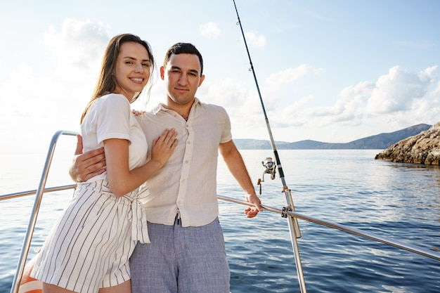 Casal feliz em um iate no verão em férias românticas