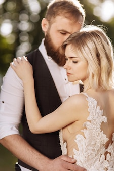 Casal feliz em vestidos de noiva simples. casal de noivos. elegante casal recém-casado. elegante vestido branco sobre a noiva. conceito de casamento.